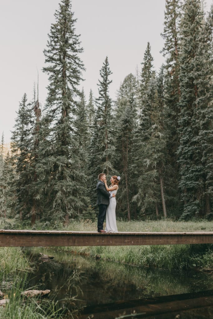 The bride is touching the grooms face. They are standing in front of tall pine trees following their destination wedding in Jemez, New Mexico.