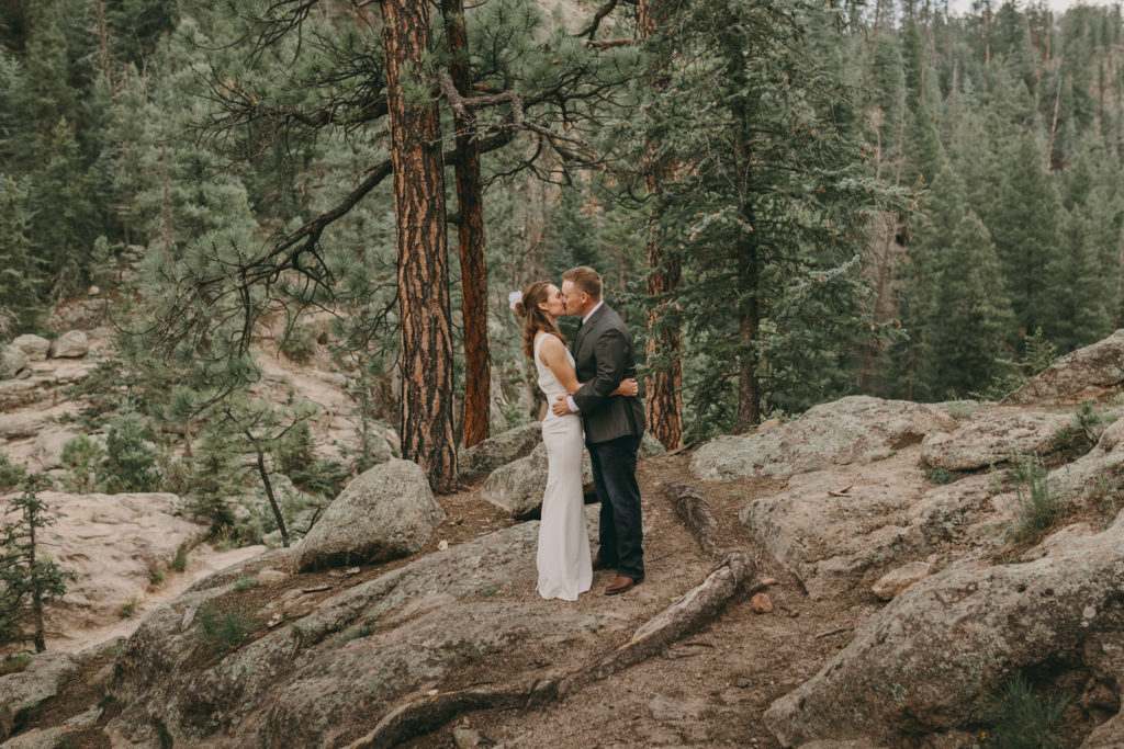 The bride and groom are kissing at their destination wedding in the Jemez Mountains