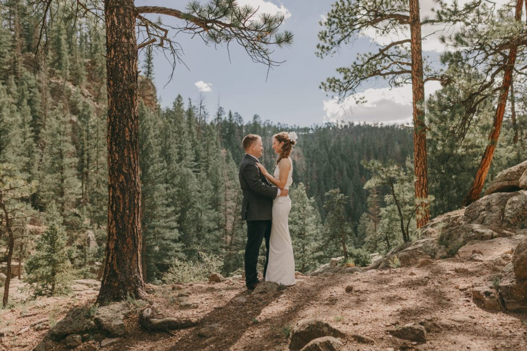 The bride and groom are holding each other at a beautiful overlook in Jemez National Forrest.