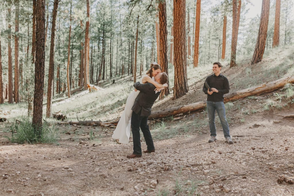 The groom is kissing the bride and picking her up off the ground.