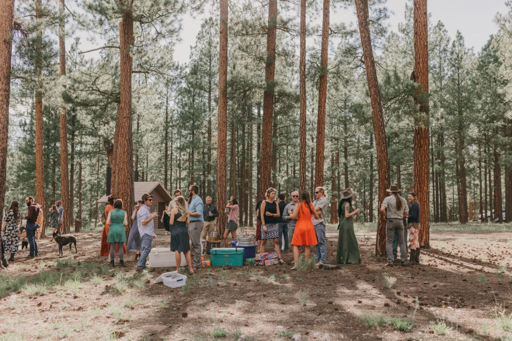 The wedding guests are standing around the kegs, talking and drinking following the wedding.